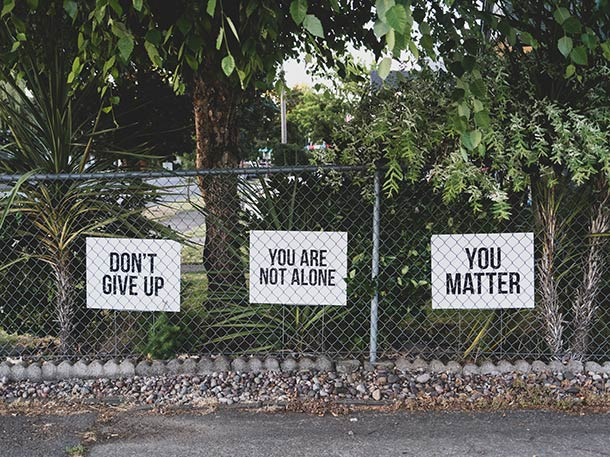 Three printed signs by the pavement reading don't give up, you are not alone, and you matter.
