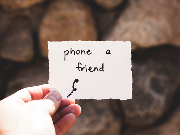 A hand holds a small piece of paper with writing on it. The writing says 'phone a friend' and there's a small drawing of a phone handset.