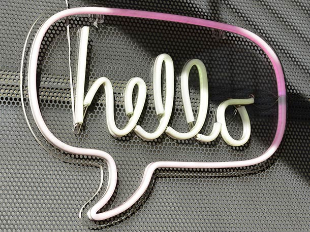 A neon speech bubble containing the text 'hello'.