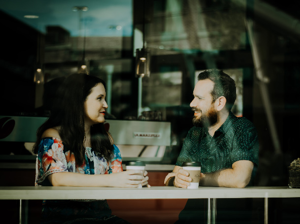 A man and a woman talk while sat at the bar in a coffee shop window.
