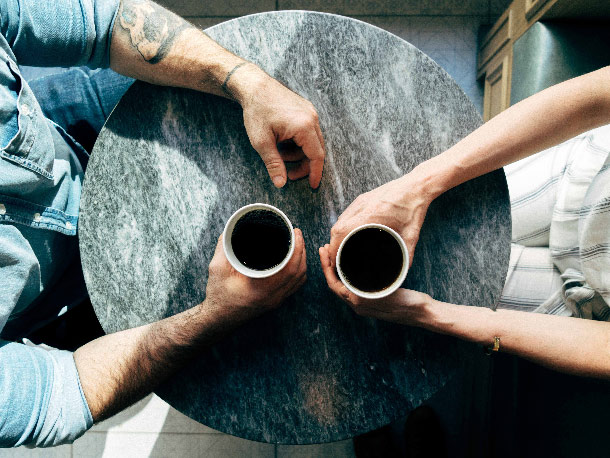 Two people sat at a round cafe table with paper cups of coffee.