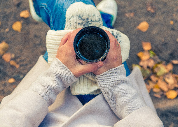 A woman sits with a coffee cup on her knee along with a crossed pair of mittens.