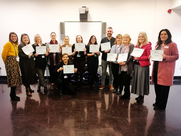 A trainer stands with 12 participants each with a certificate.